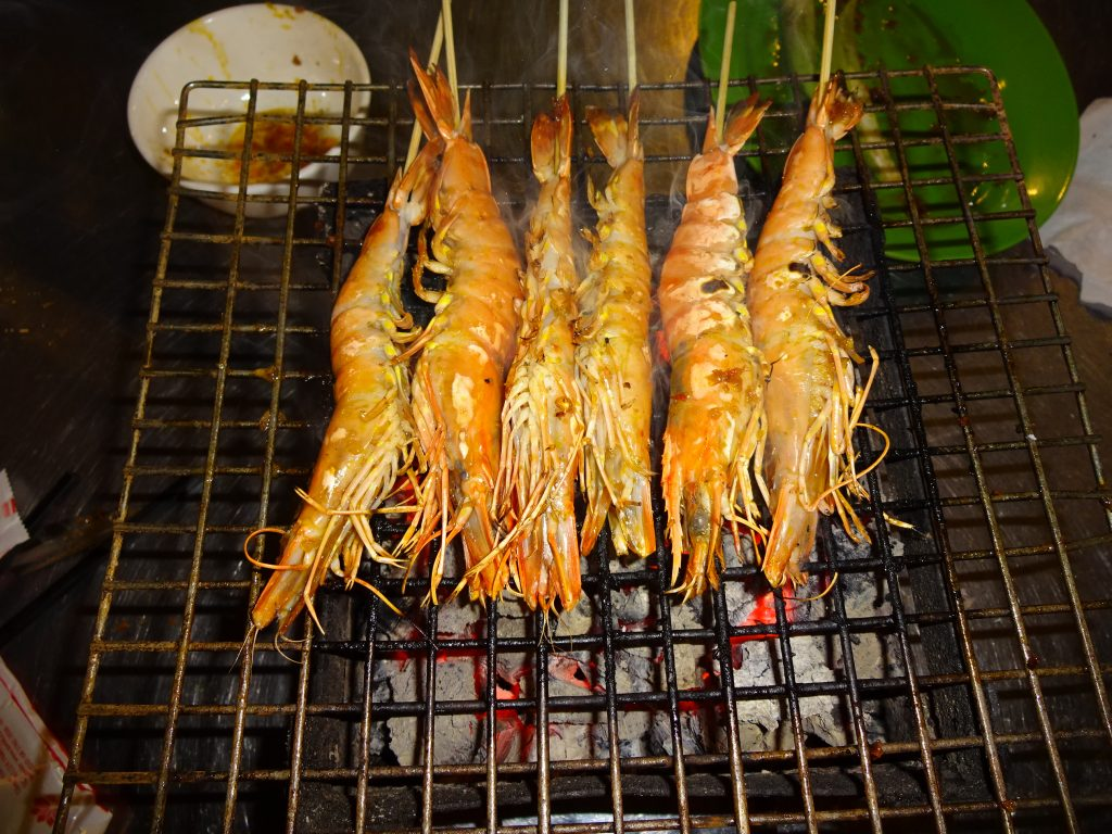 Prawns being cooked in the middle of the table.